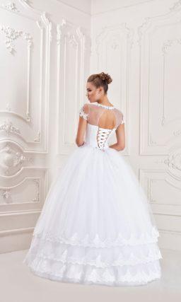 Торжественное свадебное платье с многослойной юбкой, декорированной кружевом, и закрытым лифом.