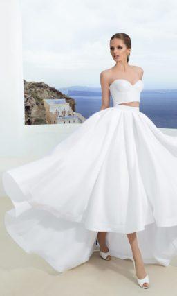 Необычное свадебное платье с укороченным топом и пышной юбкой с асимметричным подолом.