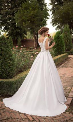 Элегантное свадебное платье с вырезом лодочкой, поясом, украшенным бантом, и пышной юбкой.