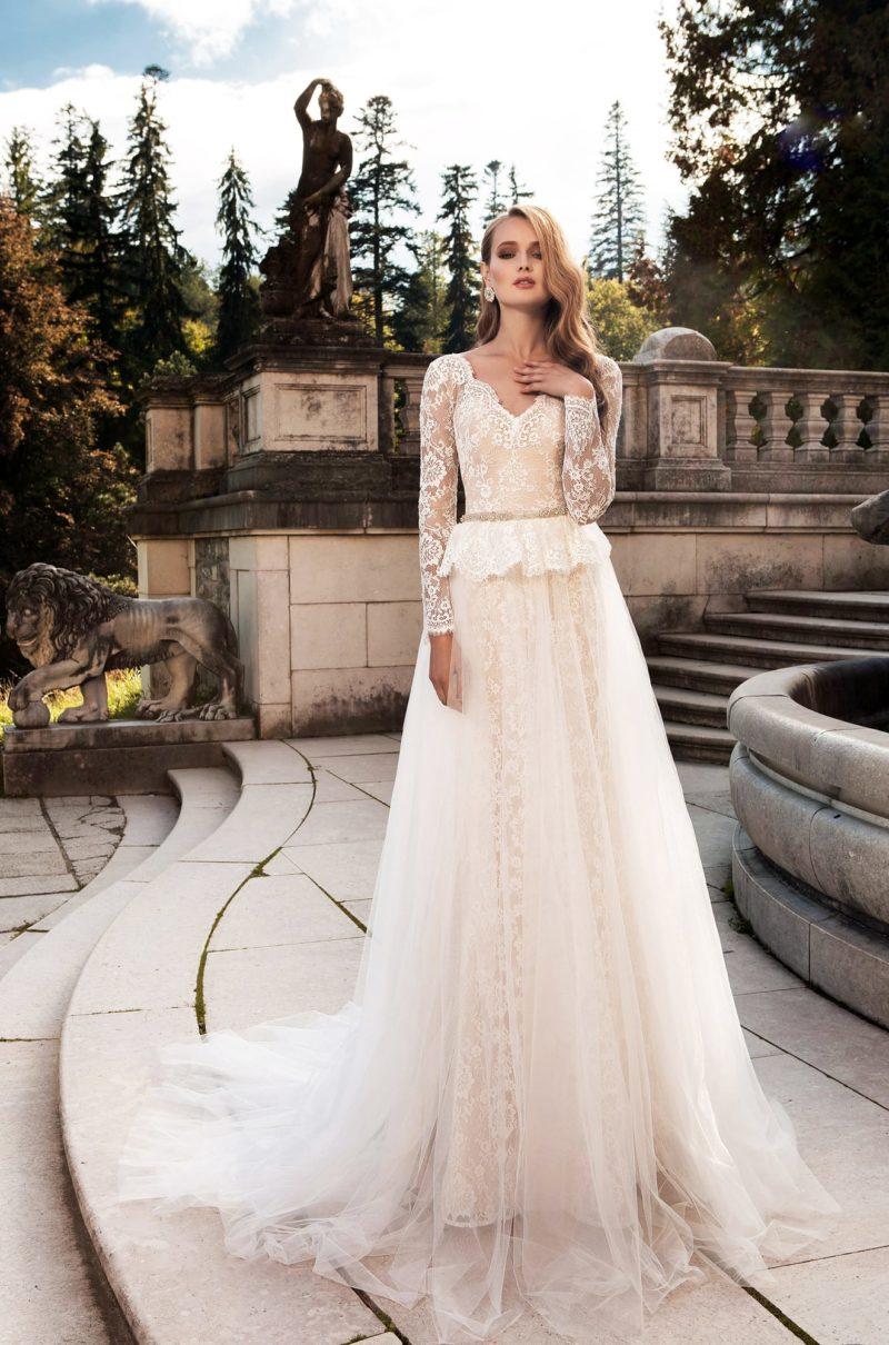Свадебное платье с бежевой подкладкой и объемной кружевной баской на уровне талии.