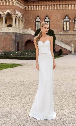 Лаконичное свадебное платье с лифом в форме сердца, с поясом, украшенным бантом, и изящной юбкой.