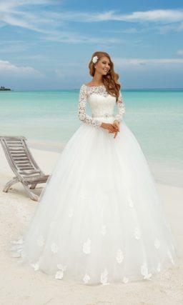 Романтичное свадебное платье с объемной юбкой, украшенной аппликациями, и длинными рукавами.