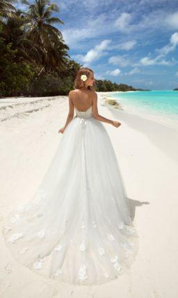 Открытое свадебное платье с лифом в форме сердца и многослойной юбкой с пышным шлейфом.