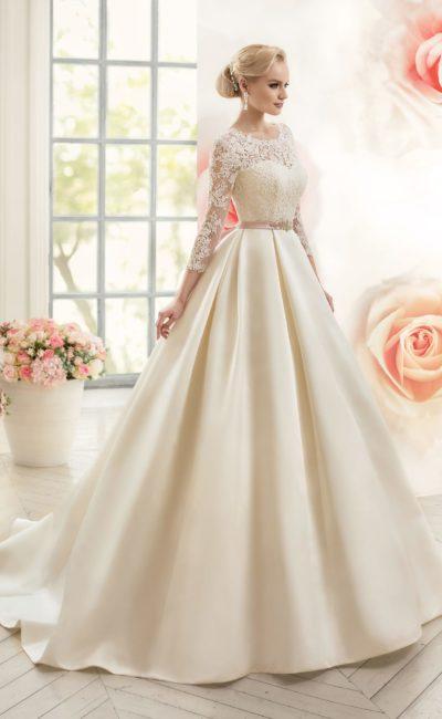 Свадебное платье с романтичным кружевным верхом, длинными рукавами и поясом из атласа.