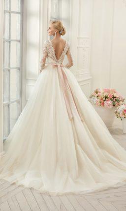 Пышное свадебное платье с закрытым кружевом верхом и поясом из розового атласа на талии.