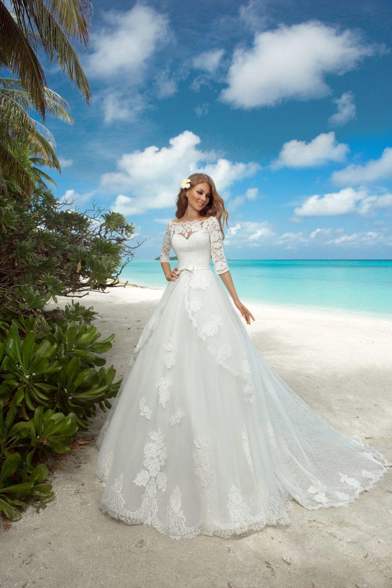 Впечатляющее свадебное платье с многоярусной юбкой со шлейфом и стильным декольте.