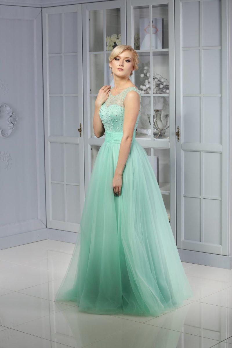 Изысканное вечернее платье мятного оттенка с закрытым верхом и многослойным подолом.