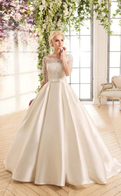 Пышное свадебное платье с атласной юбкой и верхом, полностью покрытым кружевом.