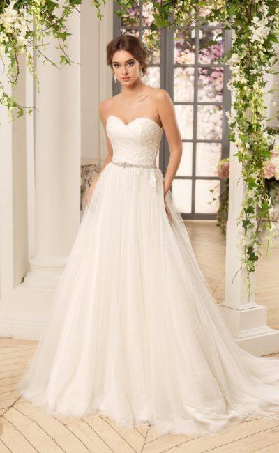 Свадебное платье с деликатной многослойной юбкой и открытым корсетом, украшенным кружевом.