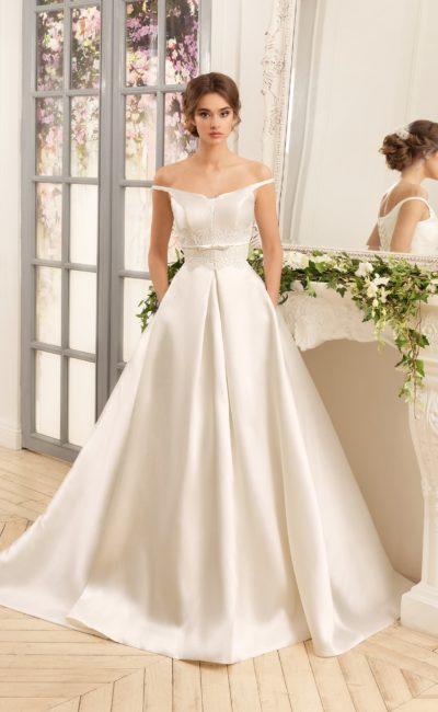 Торжественное свадебное платье с объемной атласной юбкой и портретным декольте.