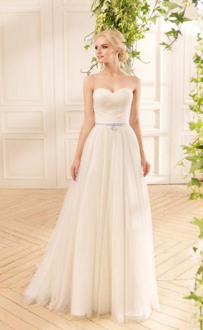 Скромное свадебное платье с отделкой драпировками и узким поясом лавандового цвета.