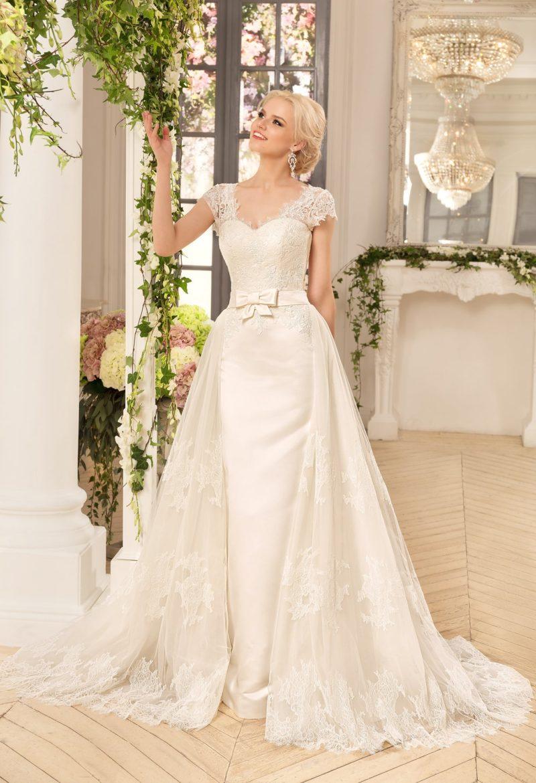Стильное свадебное платье с пышной верхней юбкой из кружевной ткани и поясом на талии.