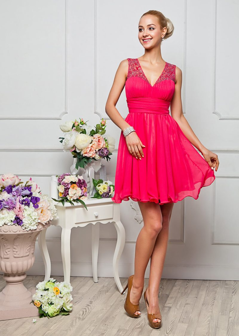 Яркое вечернее платье с многослойной юбкой длиной до колена и V-образным вырезом.