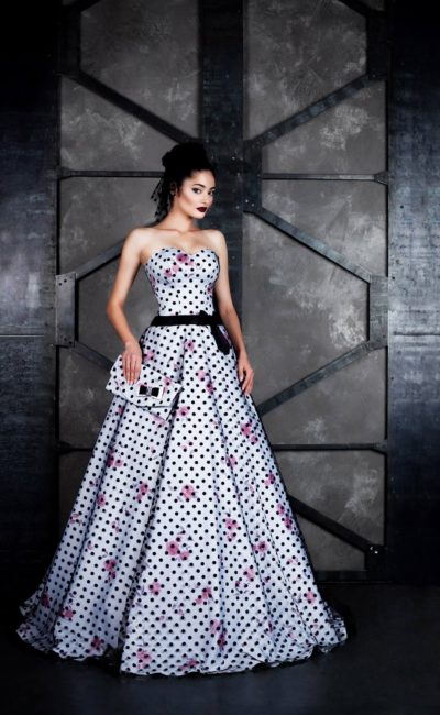 Пышное вечернее платье с рисунком в горошек и узким черным поясом.