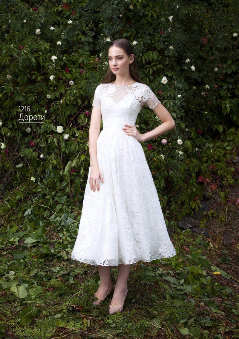 Фактурное свадебное платье длиной до колена с круглым лифом и коротким рукавом.