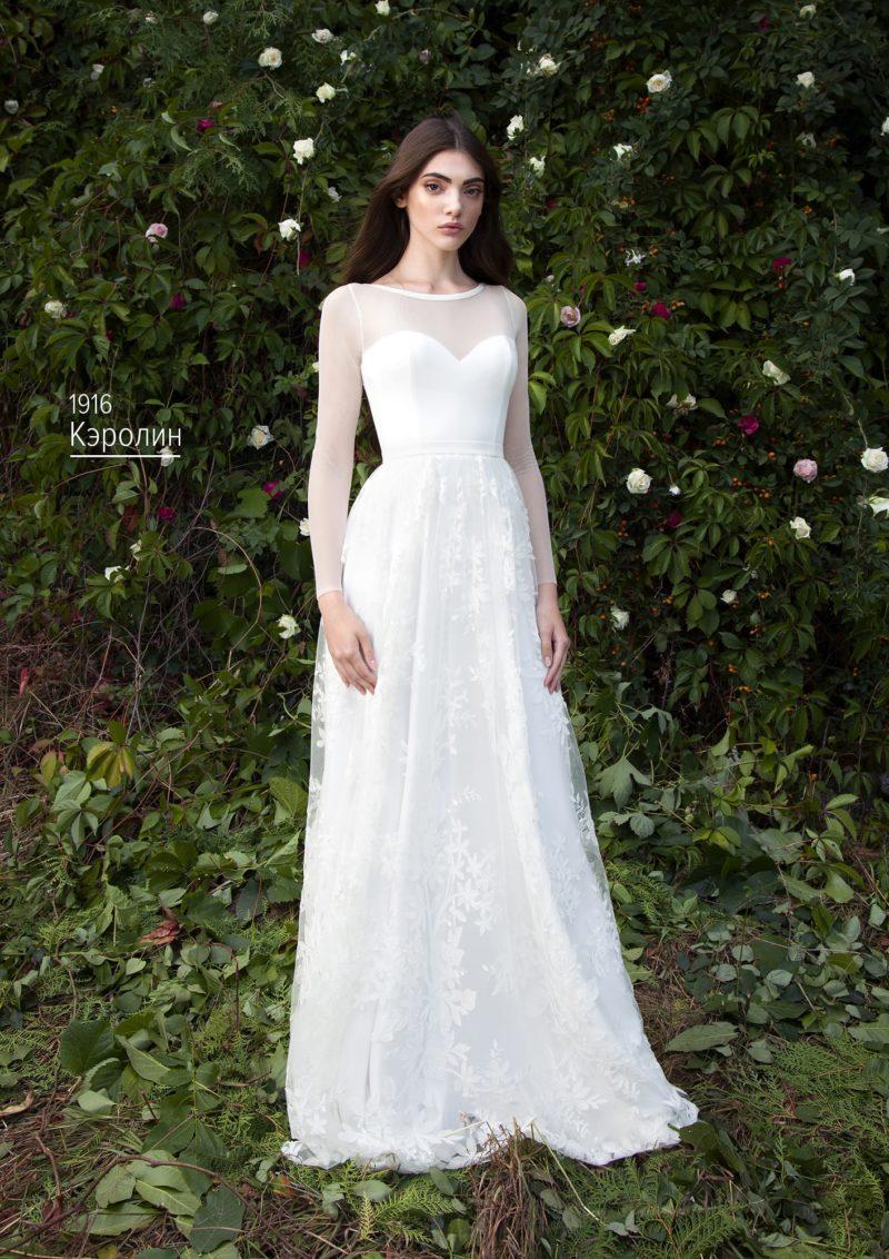 Свадебное платье с лаконичным закрытым верхом и юбкой, украшенной глянцевым кружевом.