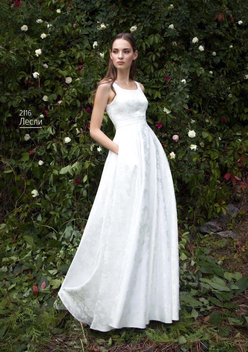 Свадебное платье из глянцевой ткани с фактурным рисунком и поясом на талии.