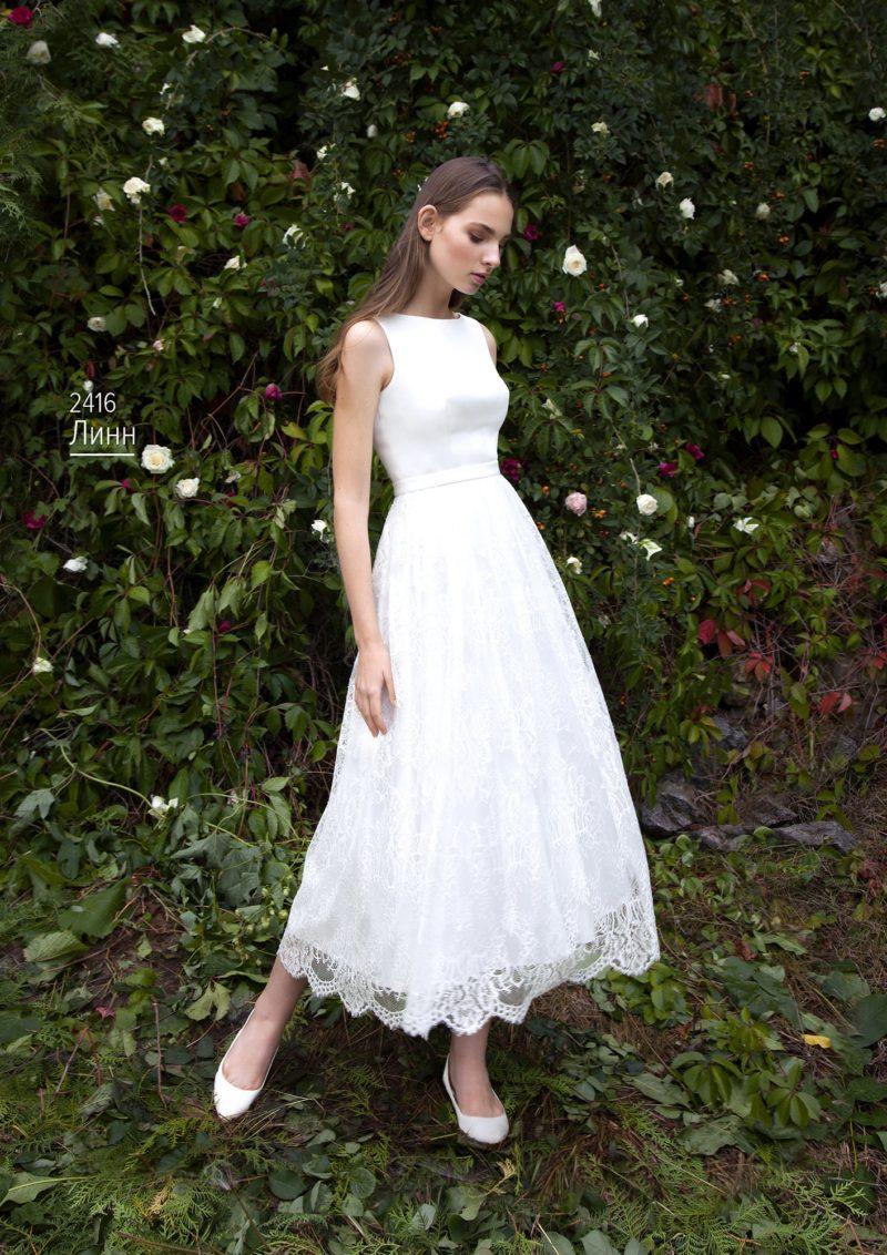 Стильное свадебное платье с атласным верхом и пышной кружевной юбкой.
