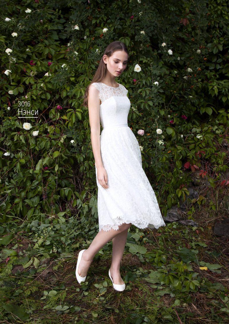 Свадебное платье с многослойной юбкой до колена и элегантным поясом на талии.
