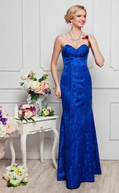 Стильное вечернее платье с открытым декольте, выполненное из элегантной синей ткани с цветочным рисунком.