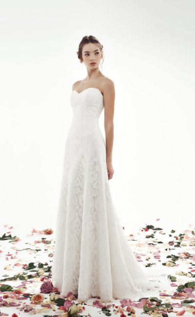 Сдержанное свадебное платье А-силуэта, декорированное кружевом по всей длине.