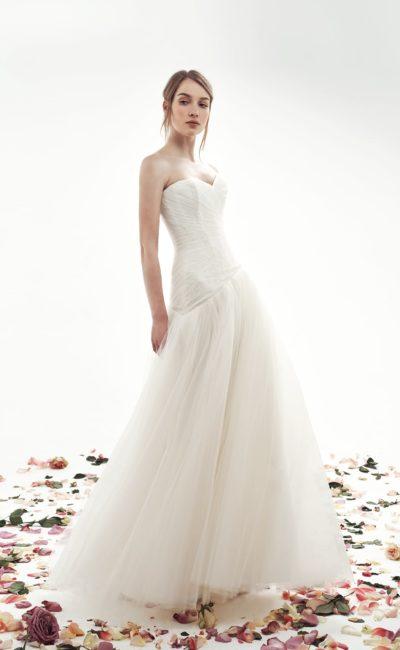 Свадебное платье цвета слоновой кости с заниженной талией и драпировками.