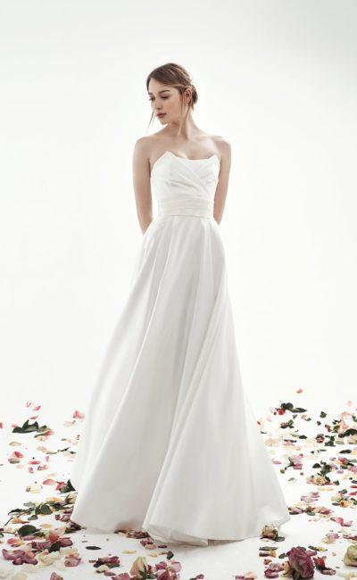 Сдержанное свадебное платье кроя «принцесса» с эффектными драпировками по лифу.