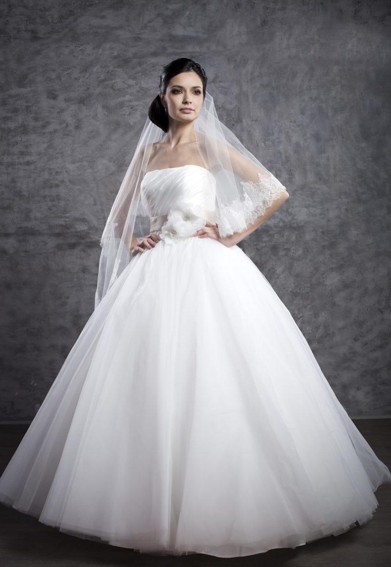 Пышное свадебное платье с открытым лифом прямого кроя и бутоном на талии.