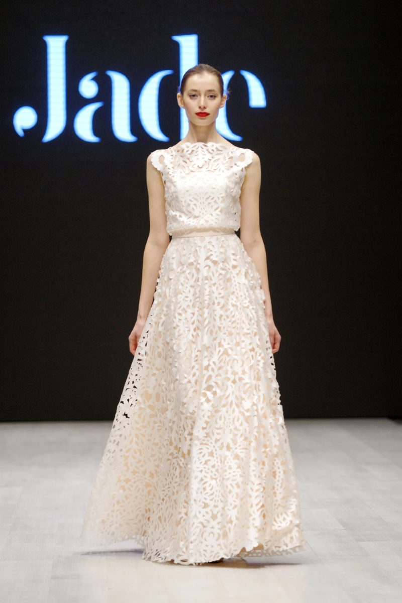 Свадебное платье цвета слоновой кости, покрытое кружевом с крупным рисунком.