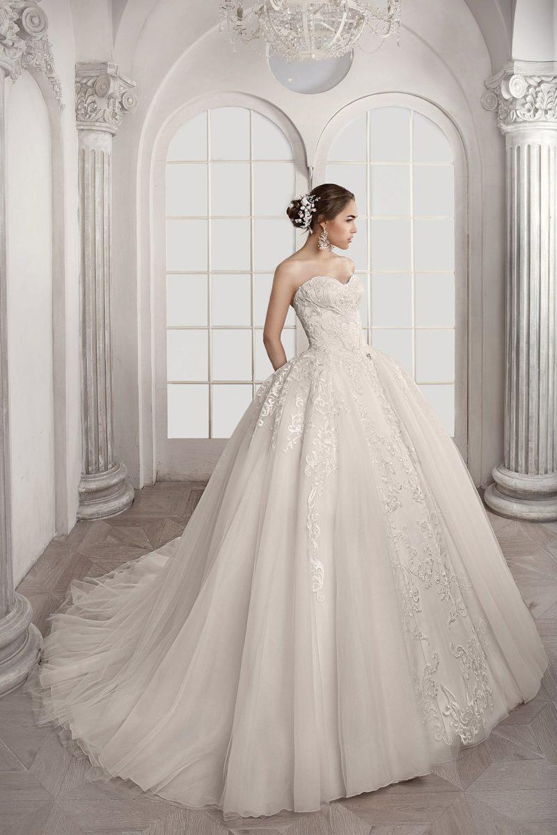 Очаровательное свадебное платье с открытым лифом и фактурной многослойной юбкой.