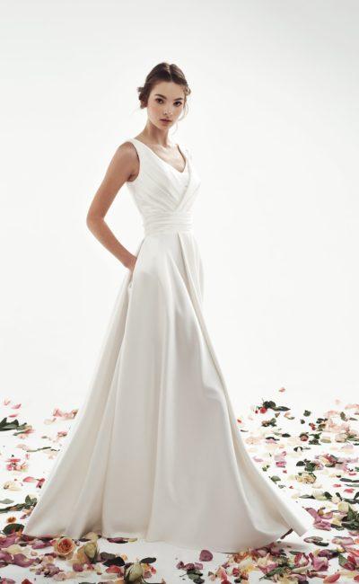 Атласное свадебное платье А-силуэта с V-образным вырезом и волнами ткани по юбке.