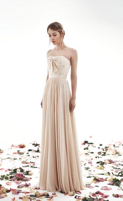 Кремовое свадебное платье прямого кроя с вертикальными складками ткани по юбке.