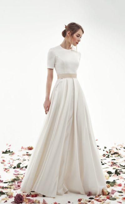 Закрытое свадебное платье с атласной юбкой цвета слоновой кости.