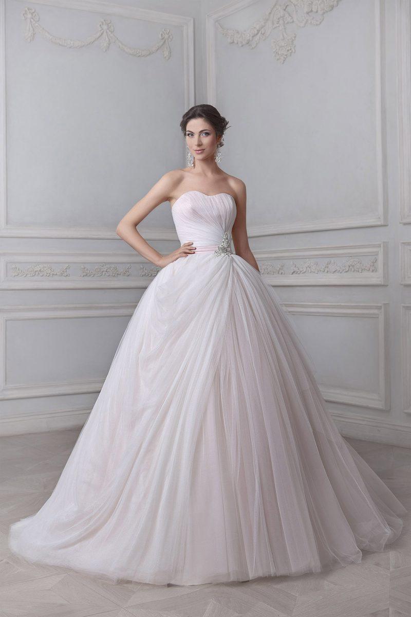 Пышное свадебное платье с нежным вырезом и роскошной отделкой из множества драпировок.