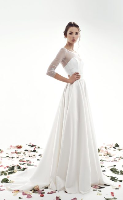 Закрытое свадебное платье А-кроя с небольшим шлейфом сзади и длинным рукавом.