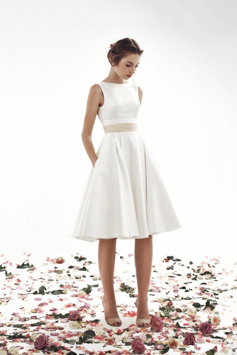 Короткое свадебное платье из белого атласа с широким золотистым поясом.
