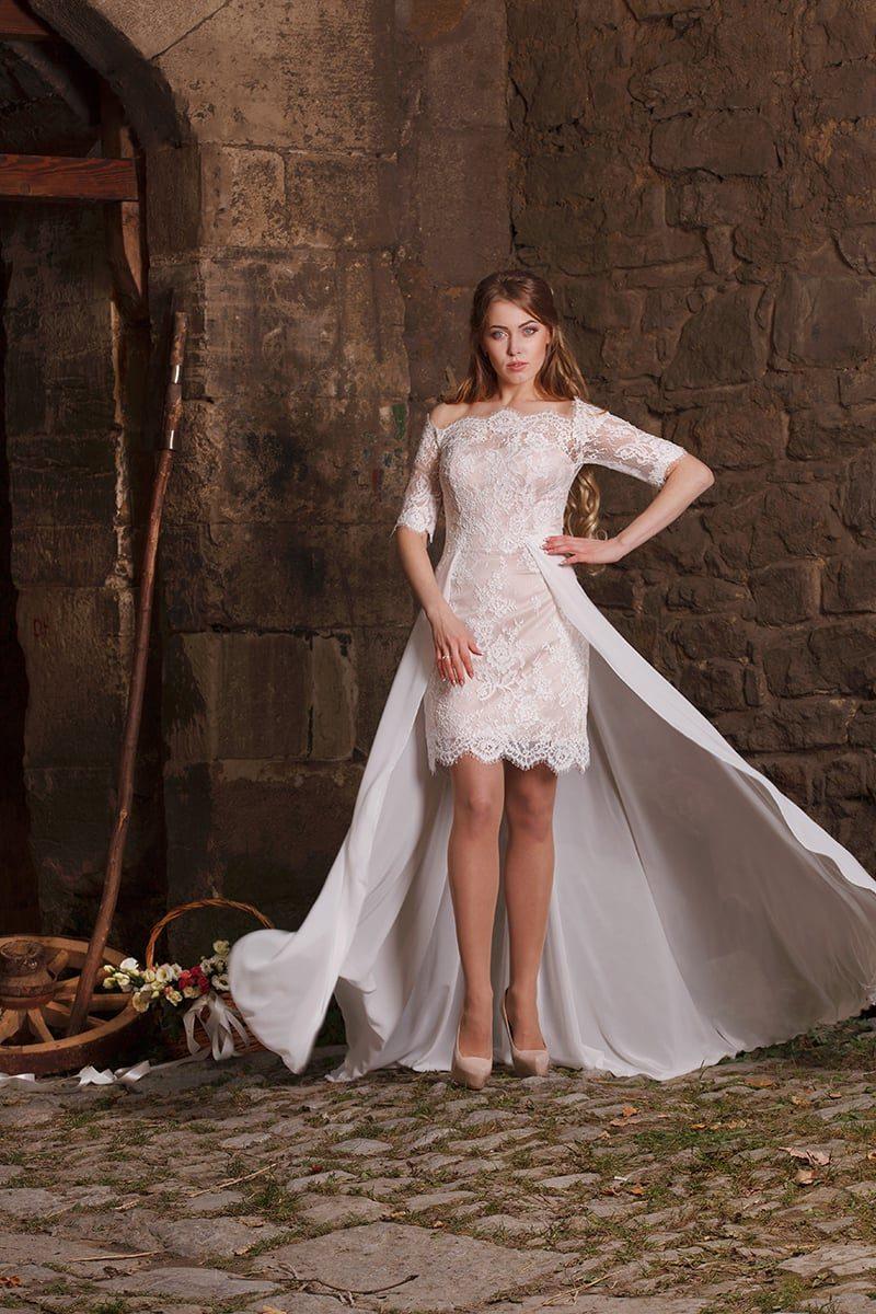Кружевное свадебное платье силуэта «футляр» с длинной верхней юбкой и короткими рукавами.