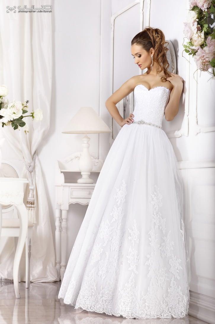 Классическое свадебное платье с узким блестящим поясом и кружевным декором.
