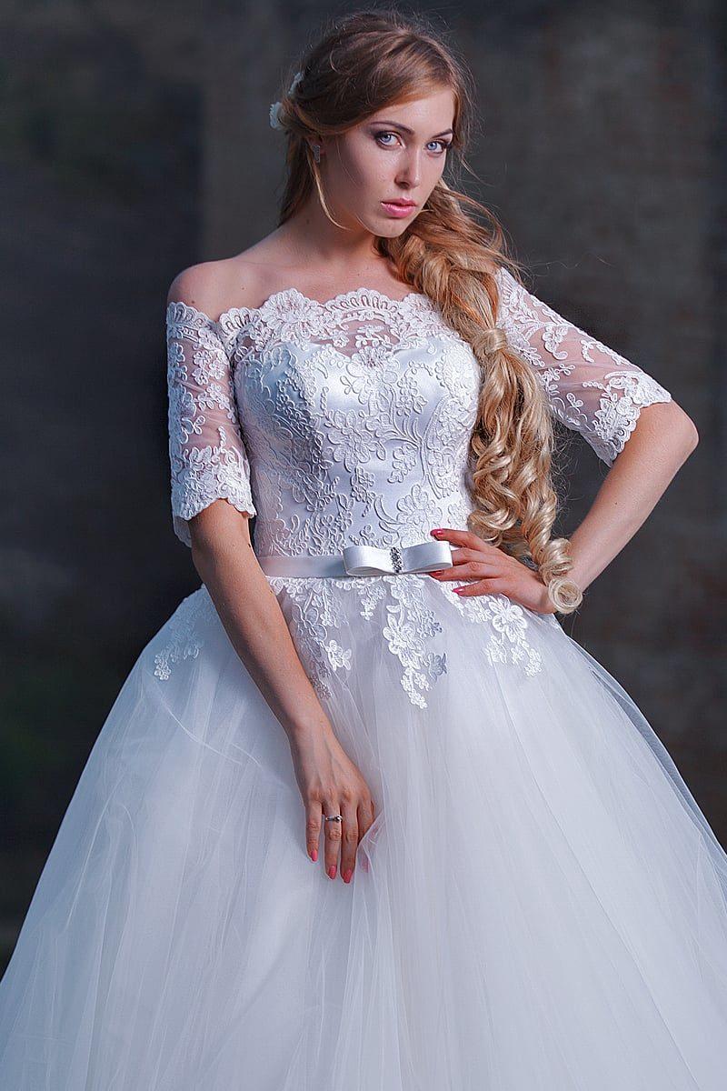 Пышное свадебное платье с портретным декольте и рукавами длиной чуть ниже локтя.