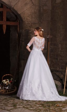 Элегантное свадебное платье с пышным подолом и изящными рукавами из тонкой ткани.