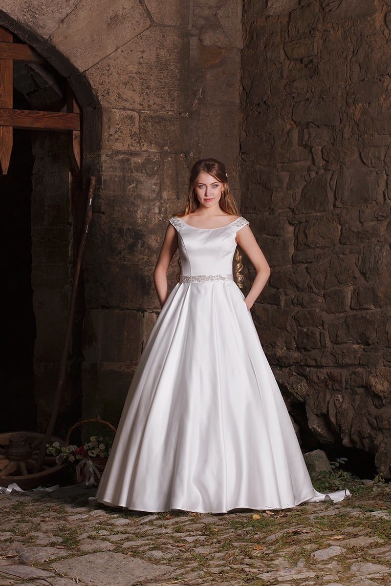 Атласное свадебное платье с округлым декольте, широкими бретелями и сияющим поясом.