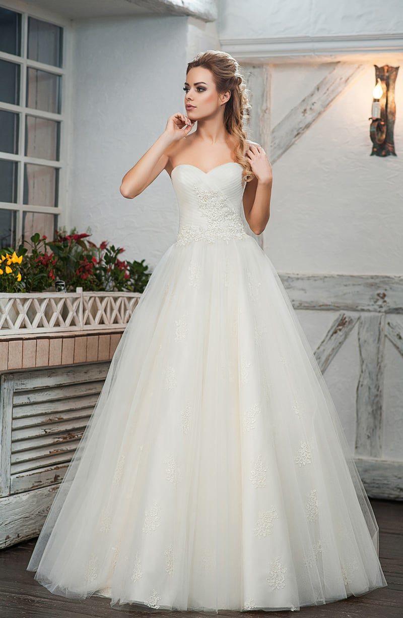 Пышное свадебное платье цвета слоновой кости с открытым декольте.