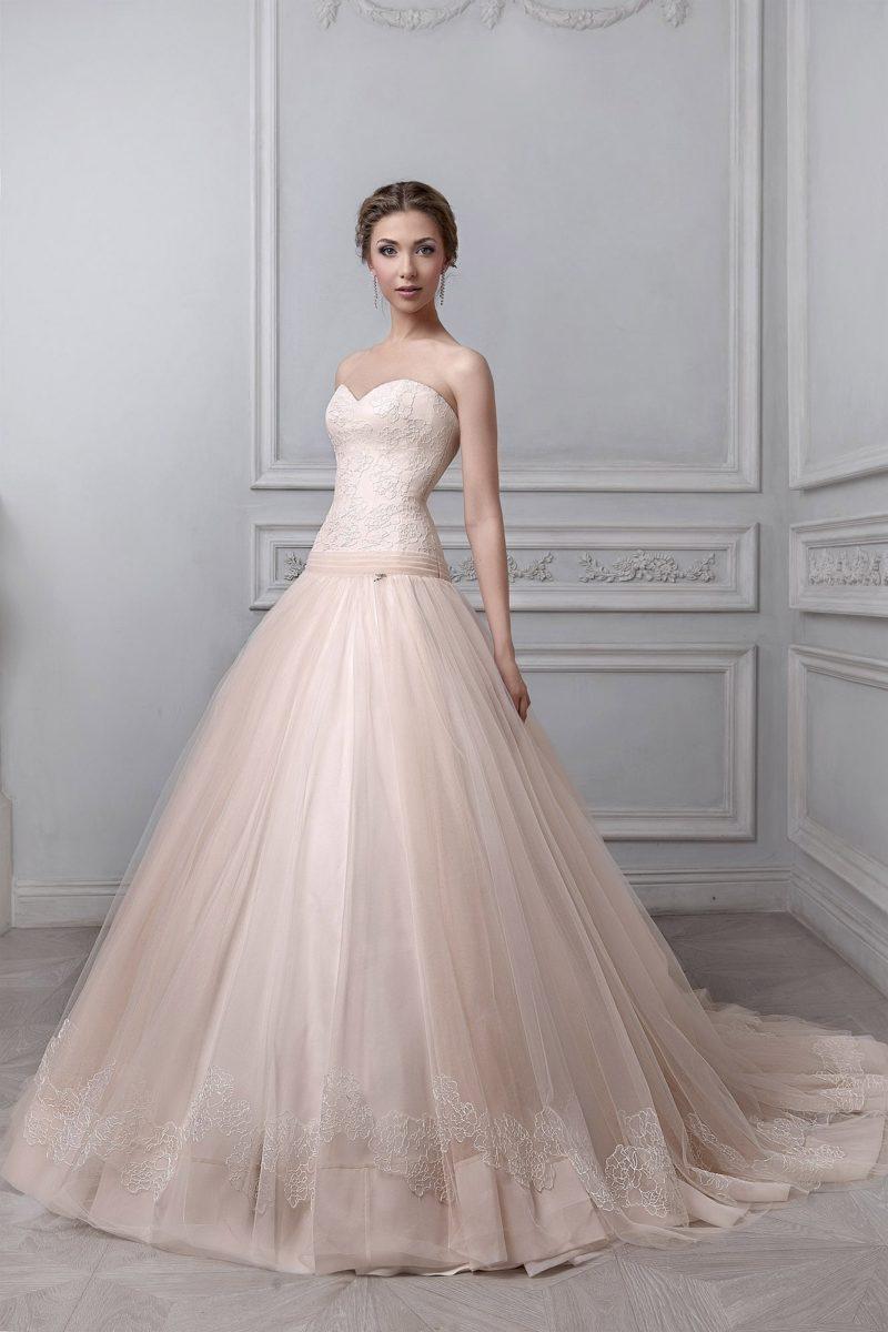 Бежевое свадебное платье пышного кроя с длинным шлейфом и нежным открытым лифом.