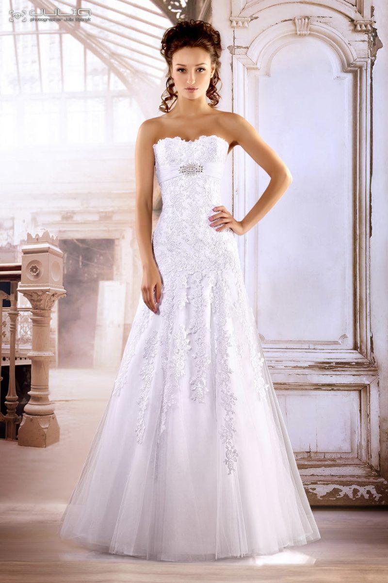 Глянцевое свадебное платье с объемной кружевной отделкой и атласным поясом.