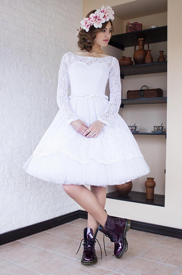 Свадебное платье с пышной юбкой до колена и длинным кружевным рукавом.