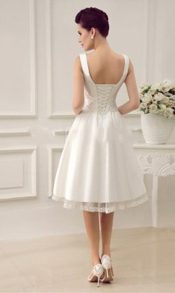 Свадебное платье с V-образным вырезом, драпировками на корсете и юбкой миди.
