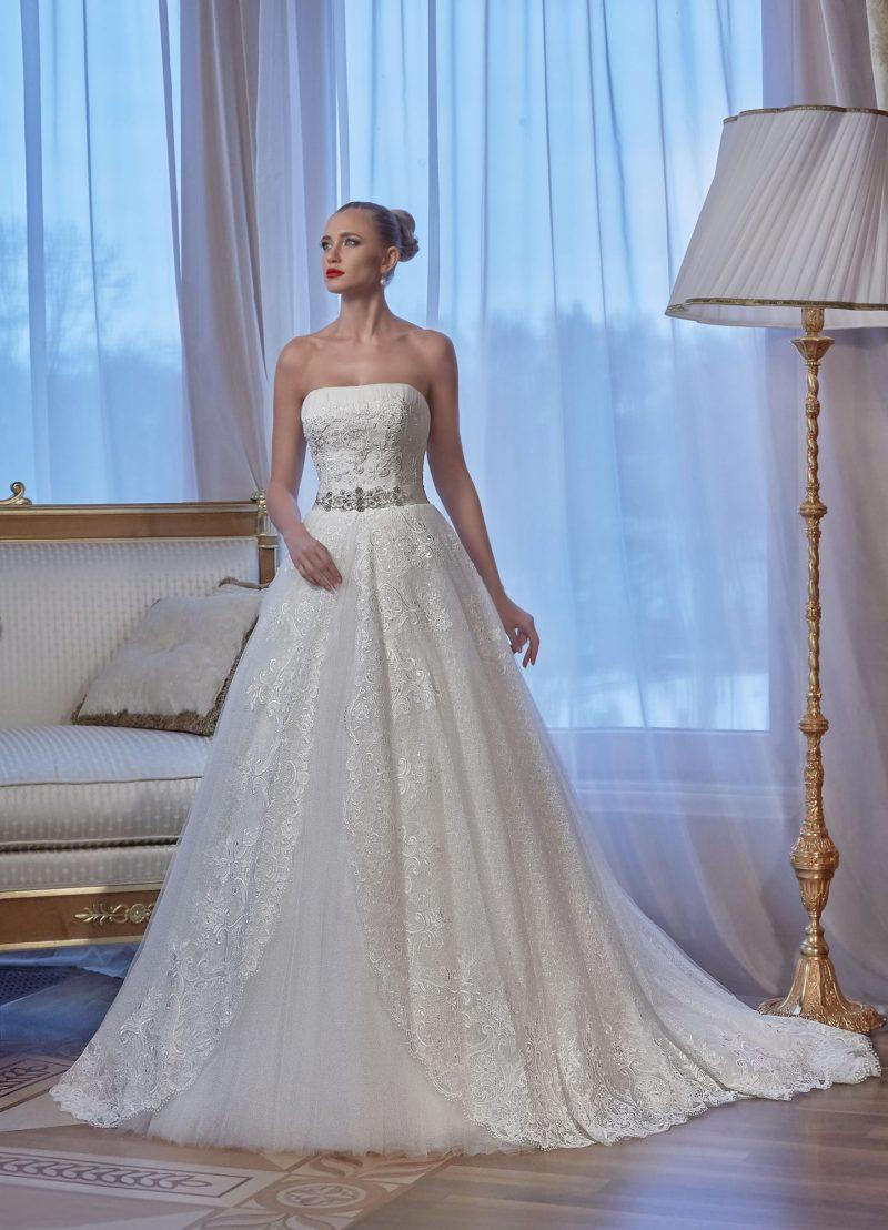 Стильное свадебное платье с лифом прямого кроя и многослойной юбкой с глянцевым кружевом сверху.