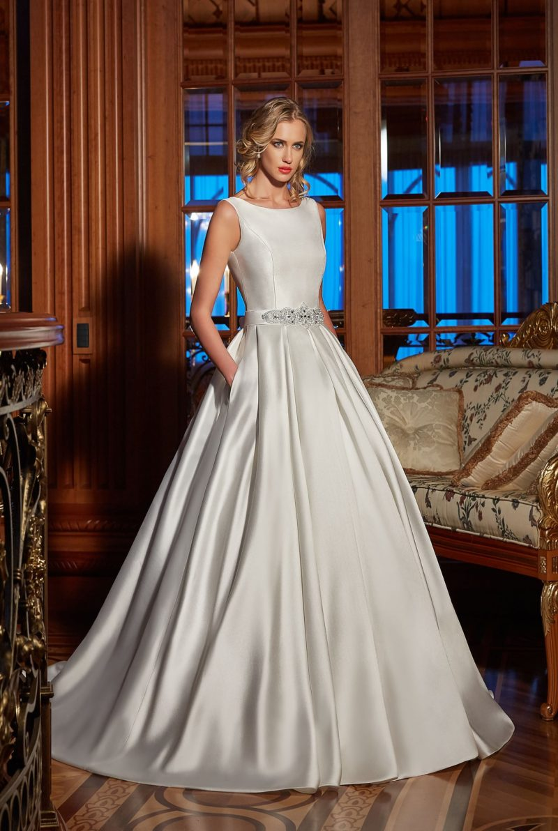 Закрытое свадебное платье из атласной ткани, украшенное кружевной вставкой сзади.