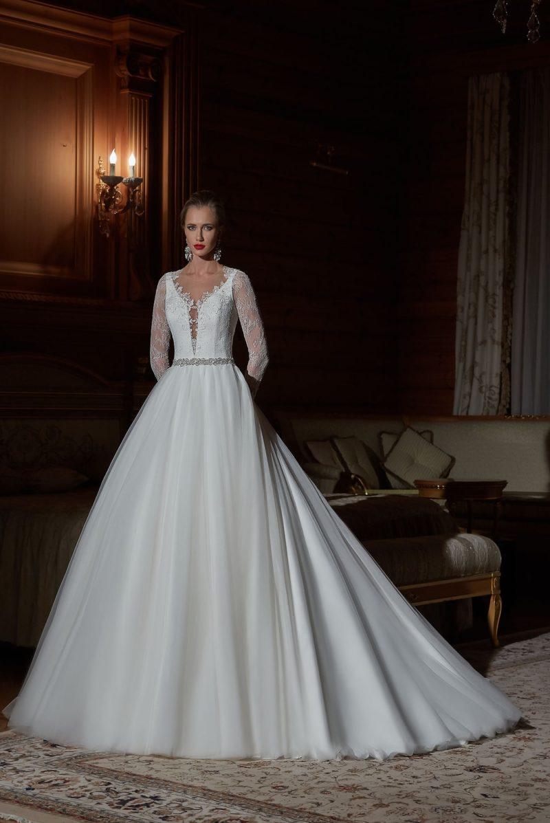 Свадебное платье с длинными кружевными рукавами и роскошной многослойной юбкой.