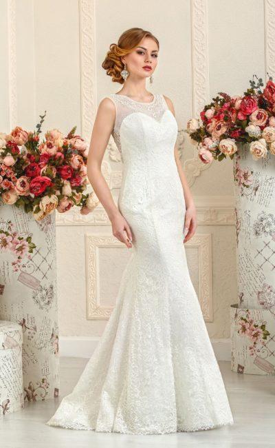 Закрытое свадебное платье силуэта «русалка», декорированное тонкой кружевной тканью.